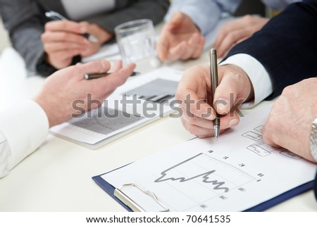 Close-up of male hands with pen over financial graphics