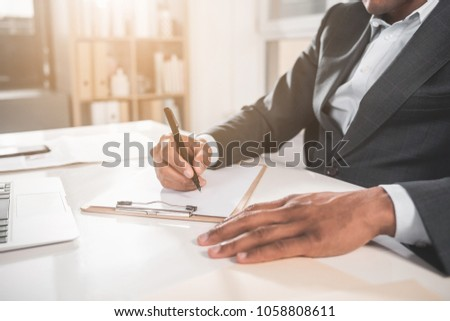 Close up of male hands writing into the document by pen. Laptop is on table. Office shelf with folders in the background. Copy space in left side