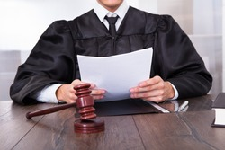 Close-up Of Male Judge In Front Of Mallet Holding Documents