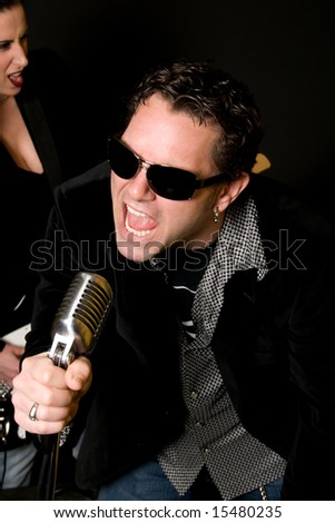 Close-up of male lead singer with retro mic and female guitar player in background