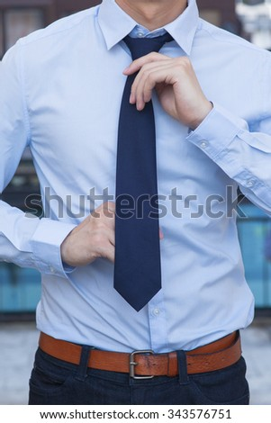 Close-up of Male office worker tying a tie  #343576751