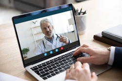 Close up of male patient talk consult with doctor using video call on laptop, man speak discuss health problem with physician on webcam virtual conference from home, online consultation concept