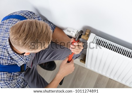 Close-up Of Male Plumber Fixing Thermostat Using Wrench At Home ストックフォト ©