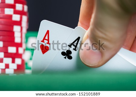 Close-up of male poker player lifting the corners of two cards