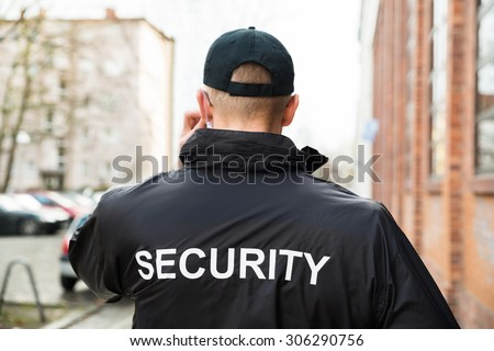Close-up Of Male Security Guard Wearing Black Jacket