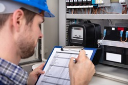 Close-up Of Male Technician Writing On Clipboard In Front Of Fuse Box