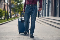 Close up of male traveler in jeans carrying trolley luggage bag while strolling down the city