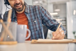 Close up of male worker in headset making notes and smiling while sitting at the table in office
