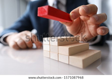Close-up of males hand adding wooden red brick to construction. Businessman building solid foundation. Macro shot. Leadership ideas and uniqueness concept