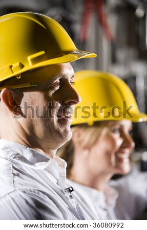 Close up of man and woman wearing hard hats