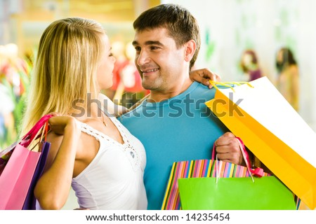 Close-up of man and woman with bags embracing each other in the department store