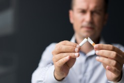 Close up of man breaking cigarette in half.  Quitting smoking habit.
