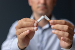 Close-up of man breaking cigarette on half while quitting smoking. Stop smoking concept.