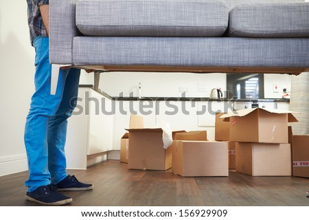 Close Up Of Man Carrying Sofa As He Moves Into New Home #156929909