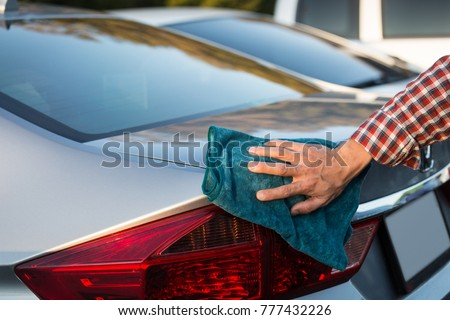 close up of man hand cleaning car with microfiber cloth. #777432226