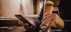 close up of man hand hold smartphone, drinking beer and reading message at bar or pub
