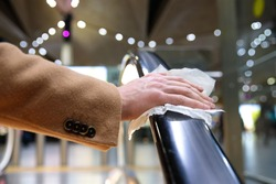 Close up of man hand holds a escalator handrail in airport terminal through a napkin, to protect yourself from contact with viruses, germs during a coronavirus pandemic, covid-19. Quarantine concept