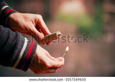 Close up of man hand lighting up a firecrackers in a burred background #1057569650