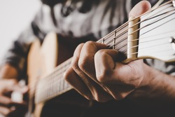 Close up of man hand playing guitar.