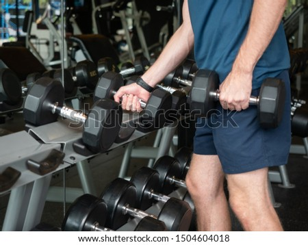 Close-up of man hand takes a dumbbell in the gym. Closeup of dumbbells, strength training equipment.