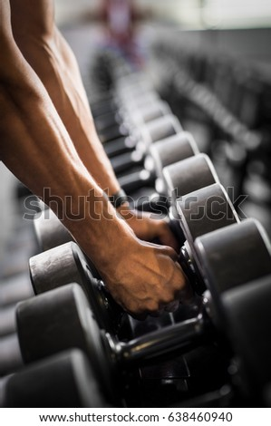 Close up of man hands holding dumbbells at gym. Strong bodybuilder lifting dumbbell. Detail of guy hands taking dumbbells from row of barbells in a gym.