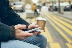 Close up of man hands holding mobile phone, using internet while sitting on the bench and drinking take away cup of coffee. Chatting with friends or family, reading latest news and updates in the web.
