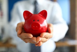 Close-up of man holding bright red piggy bank. Persons hand with container for saving money. Cash for future purchase. Money and financial well being concept