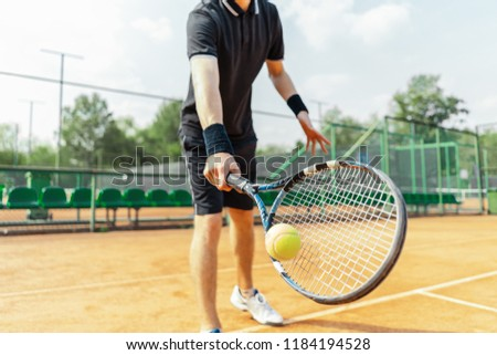 Close up of man holding racket at right hand and beating a tennis ball.