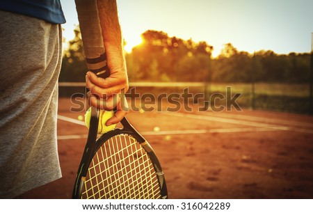 Close up of man holding tennis racket on clay court. In his hand is tennis ball. On court is sunset./Man holding tennis racket