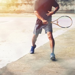 Close up of man holding tennis racket on hard court. In his hand is tennis ball. On court is sunset. Man holding tennis racket back hand. sport people outdoors concept.
