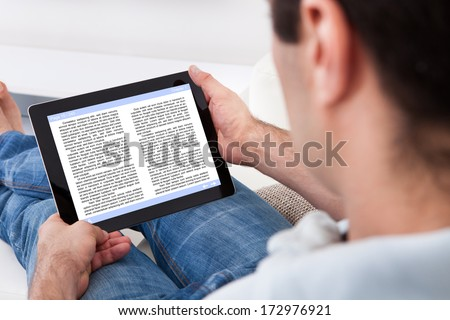 Close-up Of Man Holding Touch Screen Device Showing An E-book