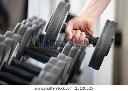 close up of man holding weight in gym