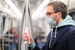Close up of man holds a handrail in public transport/subway through a napkin, to protect yourself from contact with viruses, germs during a coronavirus pandemic, covid-19. Quarantine concept