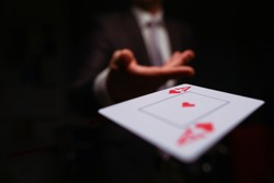 Close-up of man in presentable suit throwing playing card ace of hearts to opponent on dark background. Winning in business and risky avid player concept