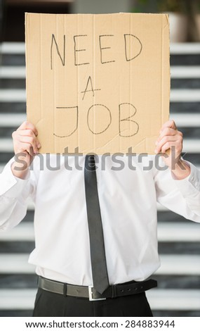 Close-up of man in suit holding sign in hands. Unemployed man looking for job.