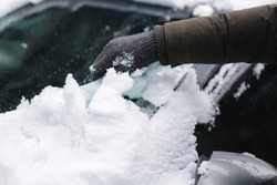 Close up of man is cleaning snowy window on a car with snow scraper. Focus on the scraper. Cold snowy and frosty morning. Black car