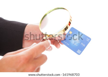Close-up Of Man Looking At Credit Card Through Magnifying Glass On White Background