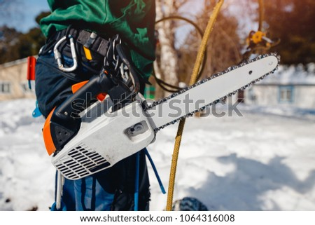 Close-up of man lumberjack holding chainsaw for cutting down trees. #1064316008