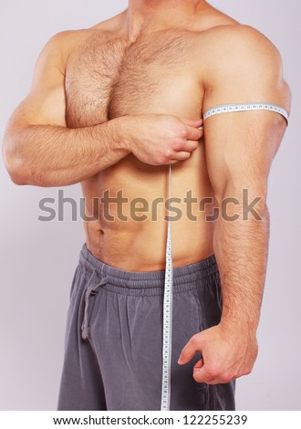 Close up of man measuring his arm biceps