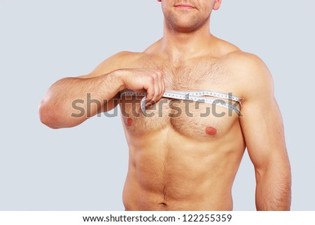 Close up of man measuring his chest over a grey background