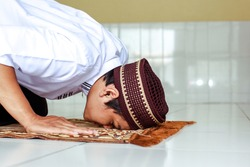 Close up of man muslim religious doing Salat with prostration pose on the prayer mat
