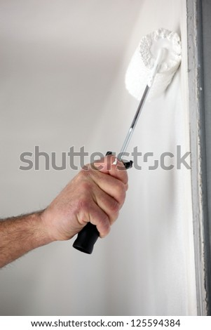 Close-up of man painting wall with roller