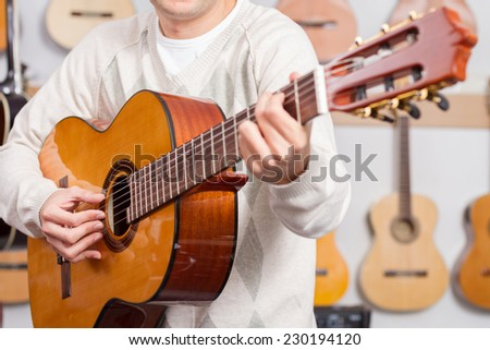 Close up of man playing a guitar with guitars background. Selective focus