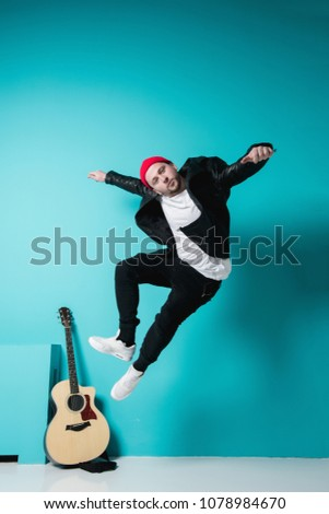 Close Up Of Man Playing Acoustic Guitar In Studio on blue background #1078984670