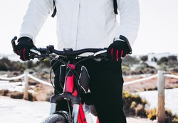 Close-up of man riding a mountain bike in the countryside, wearing black gloves and a red bike