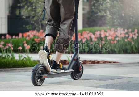 Close up of man riding black electric kick scooter at beautiful park landscape