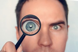 Close up of man's face with the loupe close to one eye on white background. View to round human eye through the magnifiying glass. Curious researcher. Looking through magnifier intently. Eye focus