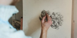 Close-up of man's hand drawing flower on easel