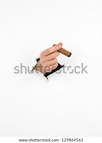 close-up of man's hand holding a cigar through a torn white paper, isolated
