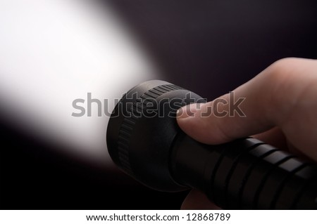 Close up of man's hand holding black  torch, with beam of light visible.